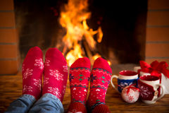 Couple near fireplace. Couple relaxing at home. Feet in Christmas socks near fireplace. Winter holiday concept Stock Photos