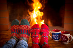 Couple near fireplace. Couple relaxing at home. Feet in Christmas socks near fireplace. Winter holiday concept stock image