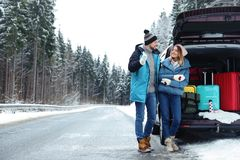 Couple near open car trunk full of luggage on road, space for text. Couple near open car trunk full of luggage on snowy road, space for text royalty free stock photography