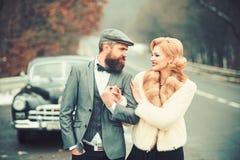 Couple near a retro car outdoors walking. stock image