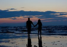 Couple near sea at sunset. Royalty Free Stock Photo
