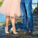 Couple near the Seine in Paris, closeup on legs. Tourists enjoying their vacation in France. Romantic date or traveling couple concept royalty free stock photography