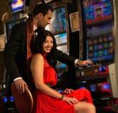 Couple near slot machine. Beautiful young couple near slot machine in a casino Royalty Free Stock Photo