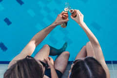 Couple near swimming pool. Cheers! Top view of young couple is having rest near swimming pool. Having fun together and drinking beer Stock Images