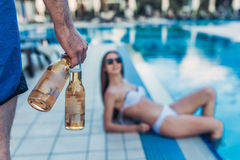 Couple near swimming pool. Young couple is having rest near swimming pool. Having fun together. Cropped image of men keeping beer in hand while women is laying Stock Photography