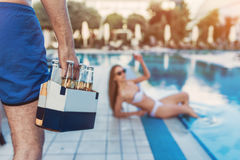 Couple near swimming pool. Young couple is having rest near swimming pool. Having fun together. Cropped image of men keeping beer in hand while women is laying Stock Images