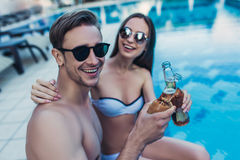 Couple near swimming pool. Young couple is having rest near swimming pool. Having fun together and drinking beer Stock Photography