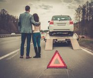 Couple near tow-truck. Picking up broken car Stock Image