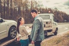 Couple near tow-truck. Picking up broken car Royalty Free Stock Photos
