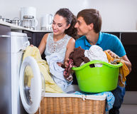 Couple near washing machine at home Stock Images