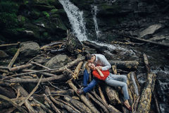 Couple near a waterfall in forest. Loving young couple near a waterfall in forest Royalty Free Stock Photo