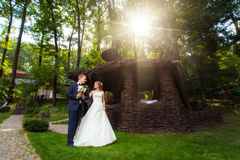 Couple near wooden arbor in park. Wedding couple in sunlight near wooden arbor in green park Royalty Free Stock Images