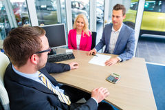 Couple negotiating sale contact for car Stock Photography