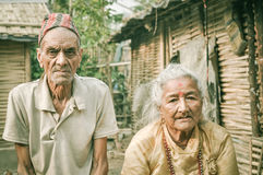 Couple in Nepal. Damak, Nepal - circa May 2012: Old man with wrinkles on his face and with cap on his head frowns and poses with woman at Nepali refugee camp in Royalty Free Stock Photo
