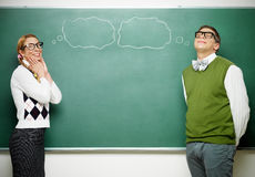 Couple of nerds in love. In front of blackboard Stock Photos