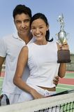 Couple by net at tennis court holding trophy portrait Royalty Free Stock Photography