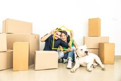 Couple in a new home. Happy couple with dog moving to a new home - Cheerful family starting a new life - Multi ethnic couple of lovers buy new apartment Stock Photos