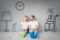 Couple New Home Moving Day House Concept. Happy couple sitting on wooden floor. Moving house day, new home and design interior concept Royalty Free Stock Photography