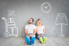 Couple New Home Moving Day House Concept. Happy couple sitting on wooden floor. Moving house day, new home and design interior concept Stock Photography