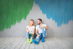 Couple New Home Moving Day House Concept. Happy couple sitting on wooden floor. Moving house day, new home and design interior concept Royalty Free Stock Image