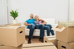 Couple In New Home Relaxing On Couch Royalty Free Stock Photography