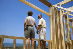 Couple at new home site. African American middle aged couple holding hands in new home construction at beach