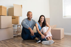 Couple in new home. Young multiethnic couple with piles of cardboard boxes after buying a new apartment. African american men embrace his smiling girlfriend Stock Photography