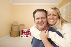 Couple in New House with Boxes and Sold Sale Sign Stock Photos