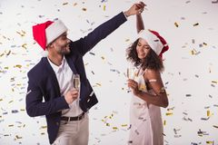 Couple with New Year mood. Beautiful Afro American couple in Santa hats and elegant clothes holding glasses of champagne, dancing and smiling, on white Stock Photography