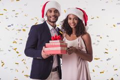 Couple with New Year mood. Beautiful Afro American couple in Santa hats and elegant clothes holding presents, looking at camera and smiling, on white background Stock Photography
