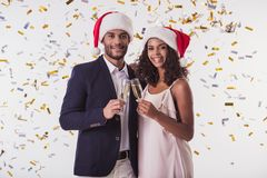 Couple with New Year mood. Elegant Afro American couple in Santa hats clinking glasses of champagne, looking at camera and smiling, on white background Royalty Free Stock Image
