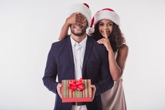 Couple with New Year mood. Elegant Afro American couple in Santa hats. Beautiful is covering her boyfriend`s eyes, showing silence sign, looking at camera and Royalty Free Stock Images