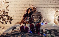 Couple on New Year`s Eve. Merry Christmas and Happy New Year! Beautiful couple is lying in bed near Christmas tree in Santa Claus hats and hugging. Enjoying royalty free stock photos