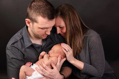 Couple with newborn baby. Happy young couple with newborn baby boy; dark studio background stock photography