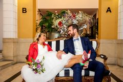 Couple of newlyweds sit on a hotel reception sofa. royalty free stock photography