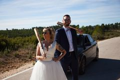 Couple of newlyweds stopped with the car on a lonely road wielding baseball bats stock images