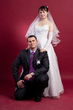 Couple newlyweds in wedding dress and suit. Girl sitting on chair in studio isolated Royalty Free Stock Photography