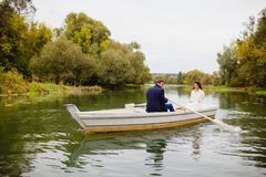 Couple newlyweds in the white boat. Beautiful couple newlyweds in the white boat at the background of autumn nature Stock Photo