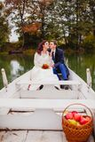 Couple newlyweds in the white boat. Beautiful couple newlyweds in the white boat at the background of autumn nature Royalty Free Stock Images