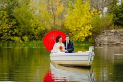 Couple newlyweds in the white boat. Beautiful couple newlyweds in the white boat with big red umbrella Royalty Free Stock Photos