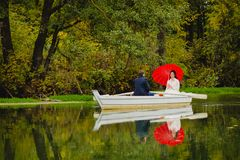 Couple newlyweds in the white boat. Beautiful couple newlyweds in the white boat with big red umbrella Royalty Free Stock Photography