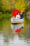 Couple newlyweds in the white boat. Beautiful couple newlyweds in the white boat with big red umbrella Stock Photo