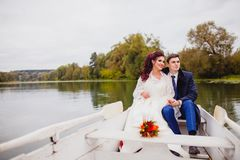 Couple newlyweds in the white boat. Beautiful couple newlyweds in the white boat at the background of autumn nature Royalty Free Stock Photography