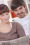 Couple with newspaper Royalty Free Stock Photos