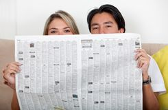 Couple with newspaper Royalty Free Stock Images