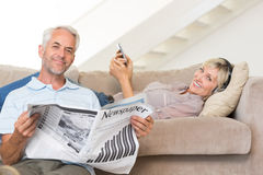 Couple with newspaper and cellphone in living room at home Royalty Free Stock Image