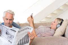 Couple with newspaper and cellphone in living room Royalty Free Stock Photography