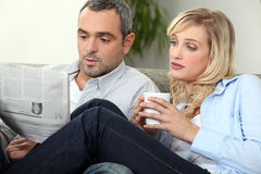 Couple with newspaper Royalty Free Stock Photo