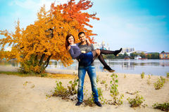 Couple next to bright orange tree in autumn Stock Images