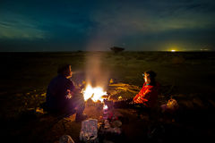 Couple next to fire at night. Stock Photos